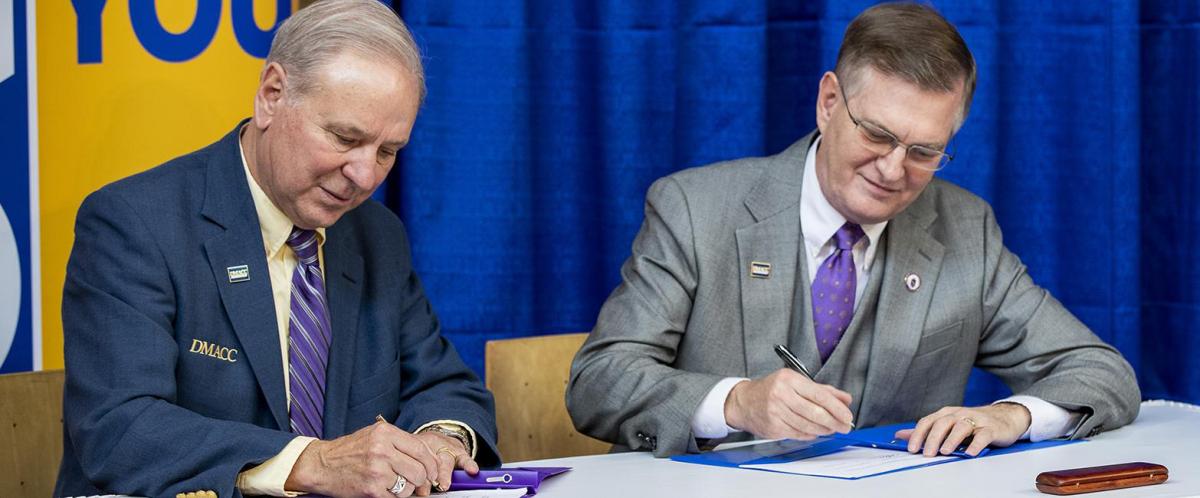 DMACC President Rob Denson and UNI President Mark Nook sign the agreement forging the UNI@DMACC program