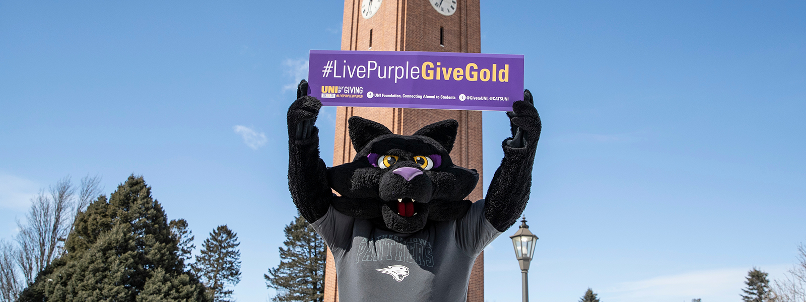 TC holding #LivePurpleGiveGold sign in front of the Campanile